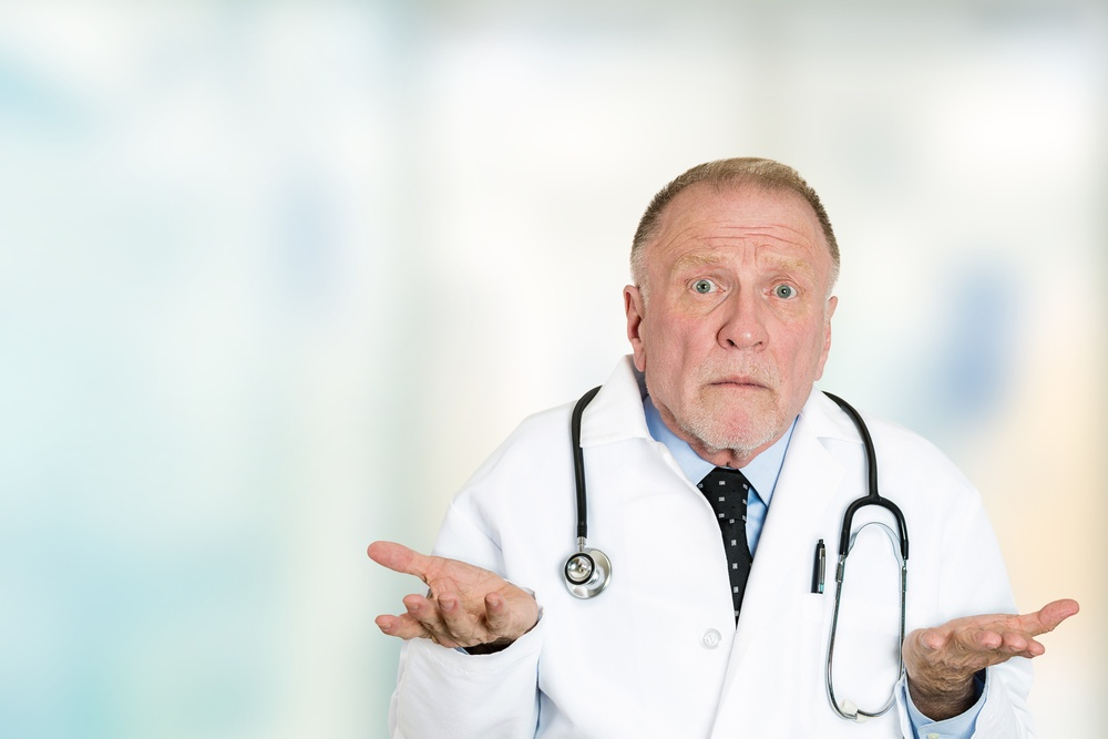 Closeup portrait clueless senior health care professional doctor with stethoscope, has no answer, doesn't know right diagnosis standing in hospital hallway isolated clinic office windows background..jpeg